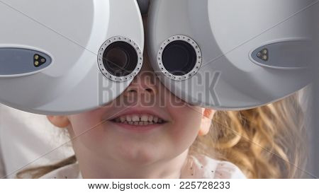 Ophthalmology Clinic - Smiling Little Blonde Girl Checks Vision Eyesight, Close Up, Telephoto