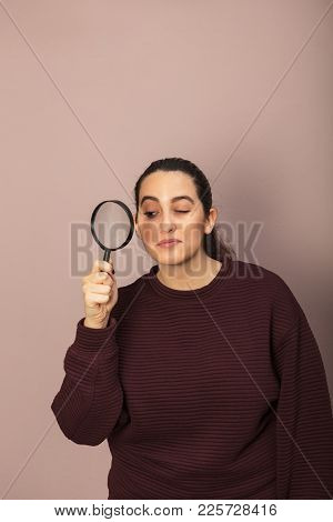Attractive Young Woman Peering Through A Magnifying Glass With One Eye In A Conceptual Image With Co