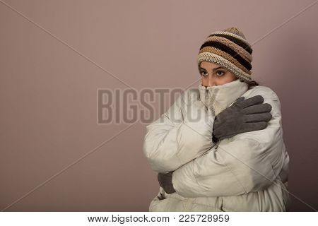 Shivering Cold Woman In Warm Winter Clothing Wearing A Thick Jacket And Knitted Cap As She Hugs Hers