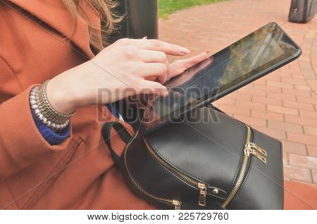 A Woman Uses A Black Tablet. Outside. Horizontal Photo. In The Frame The Hand With The Tablet