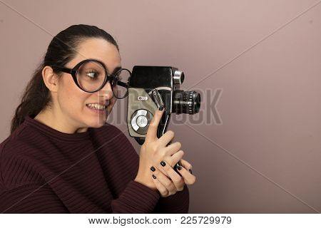 Attractive Woman Photographer Wearing Nerdy Glasses Peering Into The Viewfinder Of A Vintage Video C