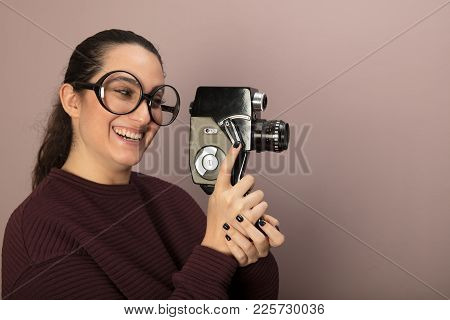 Nerdy Young Woman In Large Over Sized Glasses Laughing And Holding A 8mm Film Camera Pointed Towards