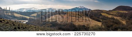 Panorama Of Borzhava Mountain Ridge In Springtime. Beautiful Countryside With Snowy Tops And Foreste