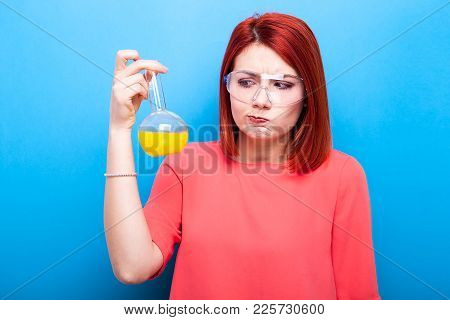 Redhair Nerd With A Flask Of Yellow Liquid In Her Hand On Blue Background
