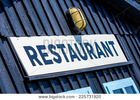 Closeup Of Restaurant Text Sign Board On Blue Wall Outside Hut