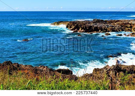 Waves Crashing Onto Volcanic Lava Rocks Taken On A Rugged Coast At The North Shore In Oahu, Hi