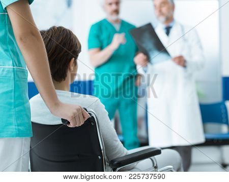 Doctors Checking A Disabled Patient's X-ray