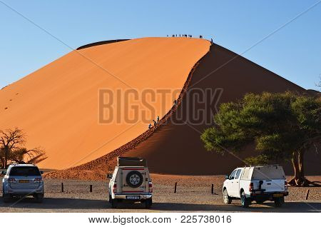 Sossusvlei, Namibia - Jan 29, 2016: Tourists Climb Dune No.45 At Sunrise, Most Popular Dune In The W