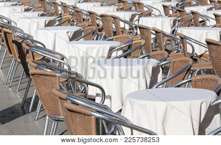 Tables Of An Outdoor Bar With White Tablecloths In A Square