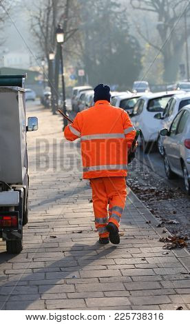 Sweeper With An Orange Jacket That Cleans The Dirty Streets Of A Big City
