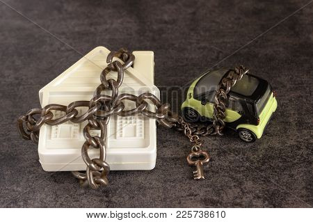 Small White House, Car, Chain And A Decorative Key On A Dark Background. Concept  -  Risks, Lose Pro