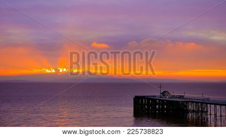 Colorful Sunrise With Sea, Penarth Pier And Sky Background In Golden And Magenta Colors.