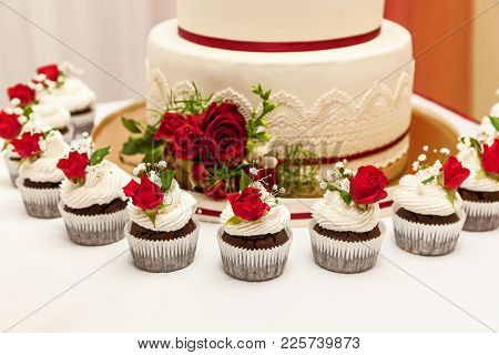 Image Of A Beautiful Wedding Cake At Wedding Reception. Wedding Cake With Red Roses