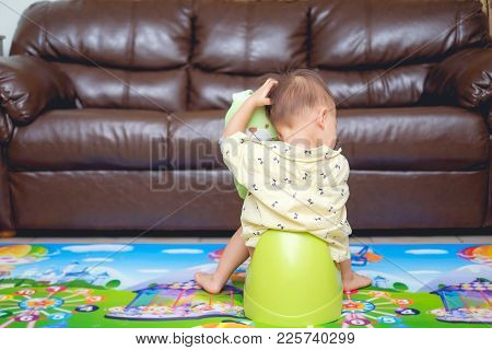 Cute Little Asian 18 Months Old / 1 Year Old Toddler Baby Boy Child Scratching Head Sitting On Potty
