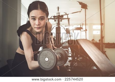 Strong Asian Skinny Woman Is Lifting Dumbbell In Fitness