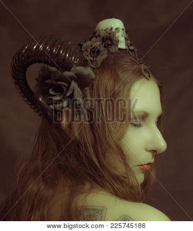 Horned Pretty Girl Posing Over Dark Background