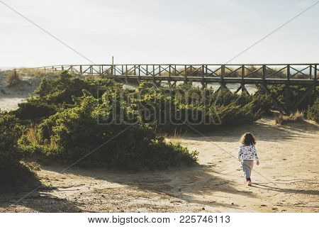 Little Girl Walking Through The Bushes And Dunes On The Beach With A Wooden Walkway Leading To The B