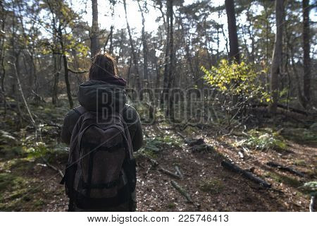 A Young Caucasian Woman In The Woods By Herself With A Backpack On And Exploring The Woods