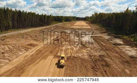Construction Of A New Road In The Forest Area. Aerial View Construction Road Place. Construction Mac