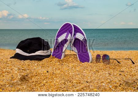 Pair Of Flip Flops, Hat And Sunglasses On A Sandy Sea Beach