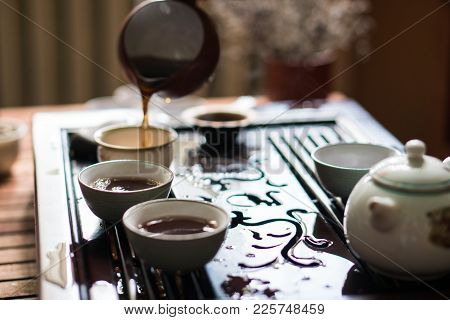 Man Pouring Puer Tea From Gaiwan Teapot At Traditional Chinese Tea Ceremony. Set Of Equipment For Dr