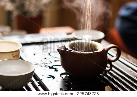 Man Pouring Puer Tea From Teapot At Traditional Chinese Tea Ceremony. Set Of Equipment For Drinking