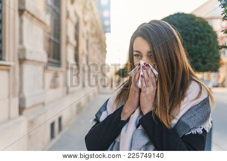 Seasonal Virus Infection. Sick Young Woman With Seasonal Influenza Blowing Her Nose On A Tissue. Wom
