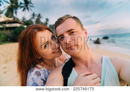 Happy Lovers Take Pictures Of Themselves On The Beach