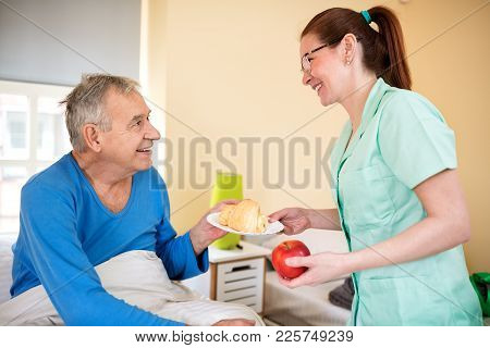 Young Smiling Nurse Brings Breakfast To Senior Patient At Nursing Home
