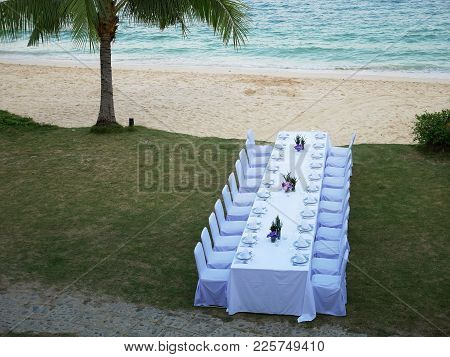 The Set Of White Table And Chairs For Private Dinner Party On The Beach Including Napkins, Knifes, S