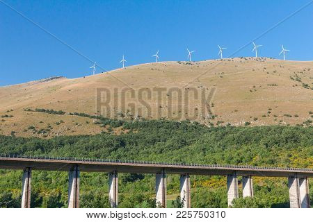 Wind Farm Under Mountain Elevated Highway Viaduct In Italian Mountains, Abruzzo
