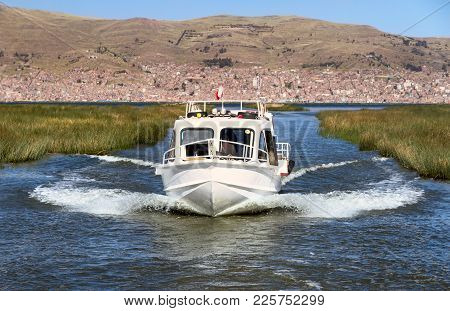 A Motor Boat On The Lake Titicaca With Puno Town In The Background, Peru