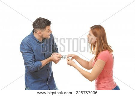 Quarreling couple fighting about money against white background
