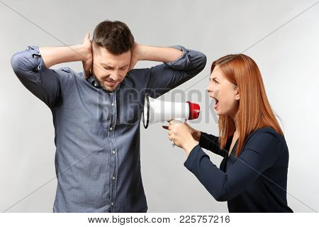 Angry woman with megaphone scolding her husband on light background