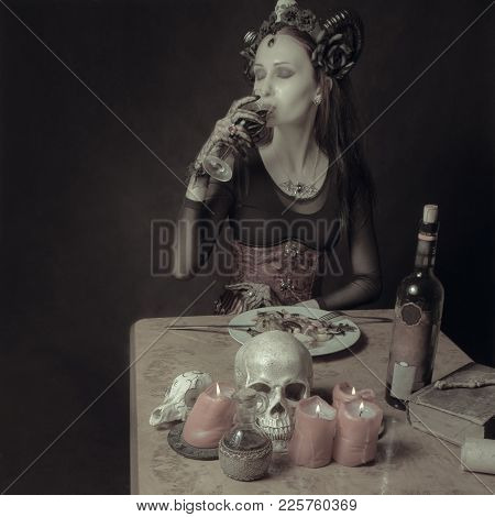 Pretty Horned Gothic Lady Drinking Wine During A Dinner