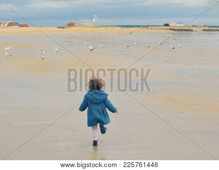 Girl In A Green Coat Run Away. Seagulls Flying Around At A Atlantic Ocean