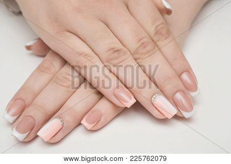 Hands With Manicured Nails Covered With Pink Nail Polish On Fur Background
