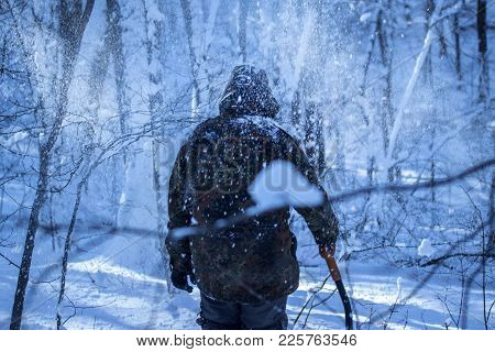 Man In Camouflage Alone In The Winter Forest At Night He Holds In His Hand A Sapper Shovel Around Fa
