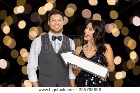 fashion, style and direction concept - happy couple with big arrow at party over lights on black background