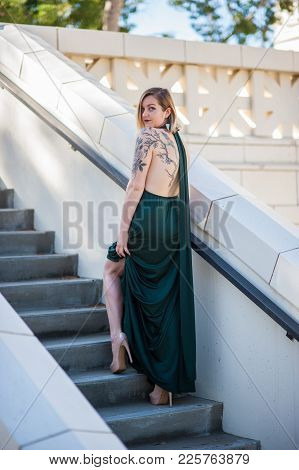 Bare Leg Showing Through Emerald Green Formal Gown Worn By Blonde Model Stepping Up Stairs To Ventur
