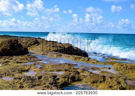 Waves Crashing Onto Volcanic Lava Rocks Which Are Tide Pools Taken At A Rugged Rural Beach In Oahu,