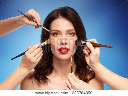 beauty and people concept - beautiful young woman with red lipstick and hands of make up artists with brushes over blue background