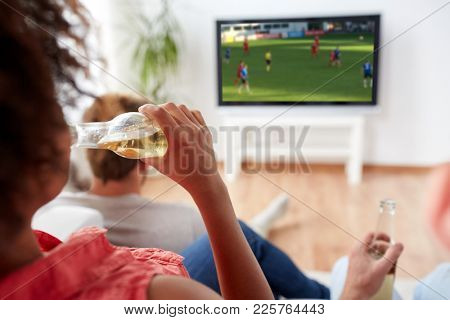 drinks, entertainment and people concept - close up of woman drinking non-alcoholic beer from bottle and watching soccer or foortball game on tv at home with friends