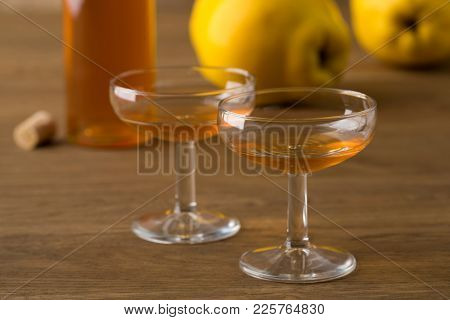 Glasses with homemade quince liqeur for dessert with fresh quinces at the background