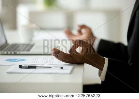 African American Calm Businessman Relaxing Meditating In Office, Peaceful Ceo In Suit Practicing Yog