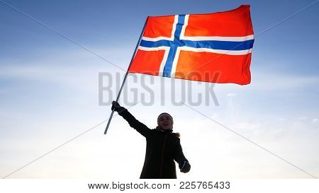 Woman with norway flag on the top point. Succesful winer consept.