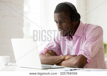 African American Man Wearing Headphones Using Laptop Looking At Computer Screen, Smiling Young Black