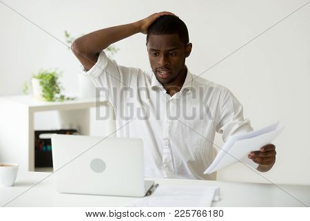 Confused African-american Businessman Having Problem With Documents Looking At Laptop At Work, Frust