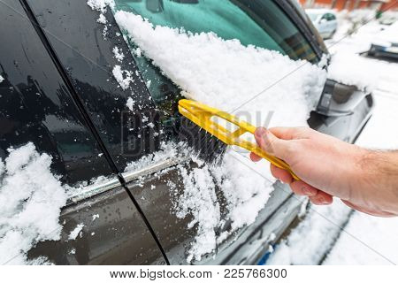 Scraping frozen snow from the car windows poster