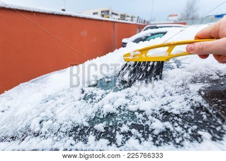 Scraping frozen snow from the car windows